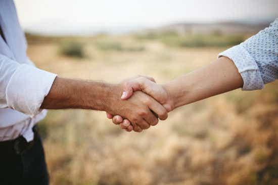 shaking hands in field
