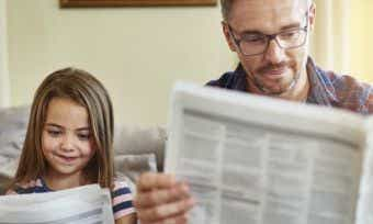 Dad and daughter reading newspaper