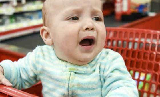 Baby crying in shopping cart - aqua crop
