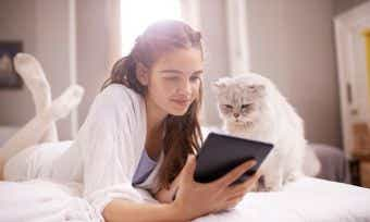 Cat on bed with tablet and girl owner