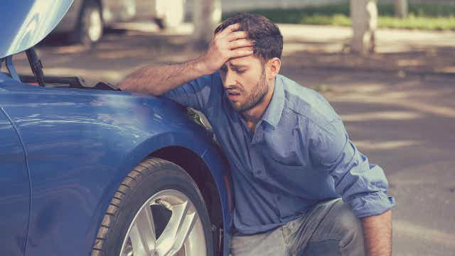 man with broken down car