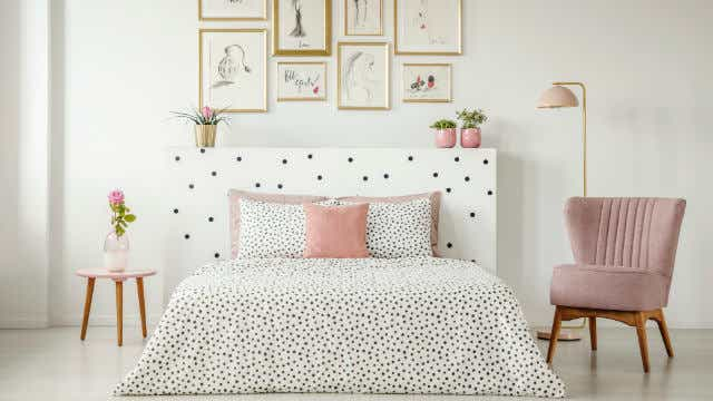 A bedroom with a polka-dotted bedspread.