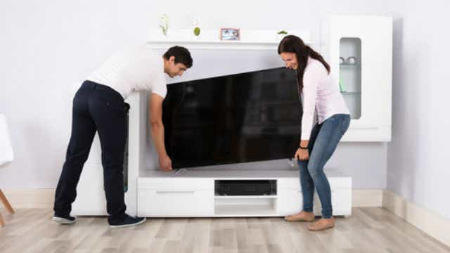 Couple installing a TV.