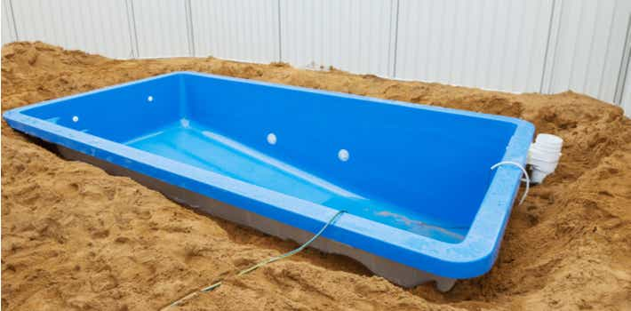 Fibreglass pool being installed after excavation.