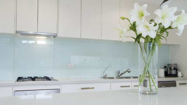 Light green glass splashback in a kitchen with a vase of flowers on the bench.