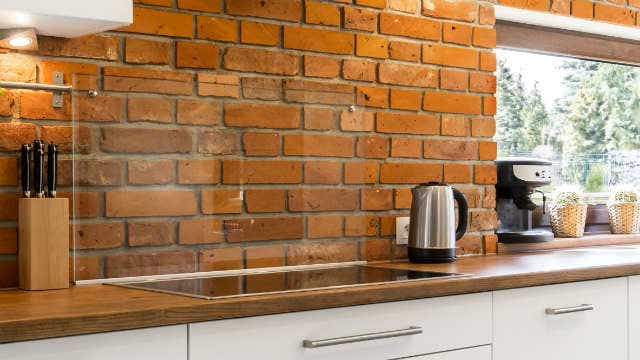 Modern kitchen corner with a stylish brick wall and a large horizontal window - Image