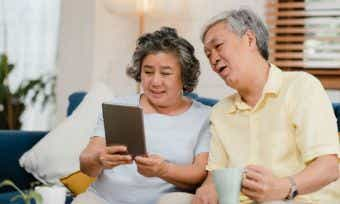 A mature couple examines their bank balance online.