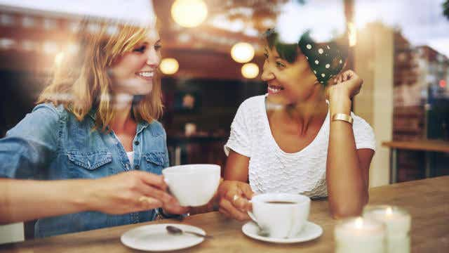 Two women drinking coffee at a cafe.