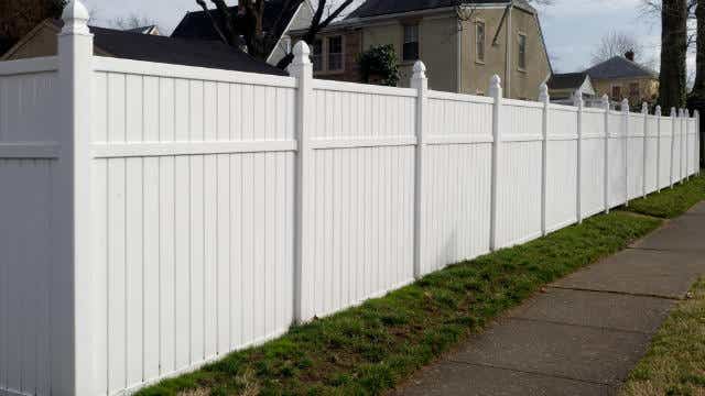 A picture of a PVC fence in a suburban street