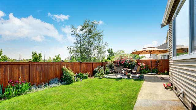 A picture of a wooden fence around a lovely garden with an outdoor setting