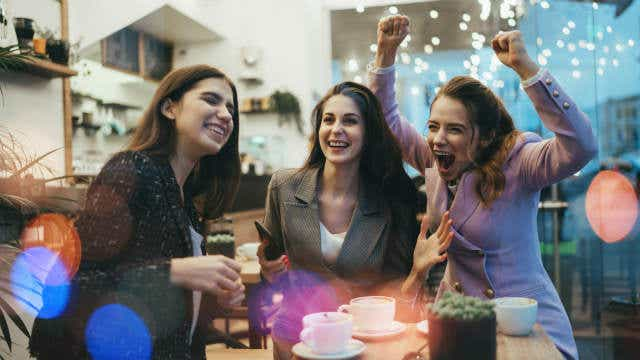 A group of smiling women celebrate at a cafe.