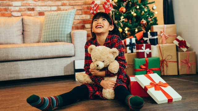 A girl sitting on the ground hugging a teddy with a Christmas tree in the background.