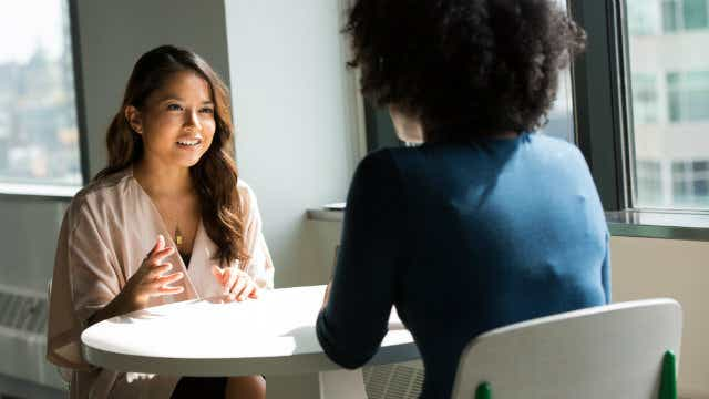 Two people talking over a table in a work situation | Canstar