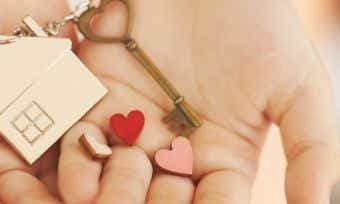 A picture of a pair of hands holding a house key with three hearts | Canstar