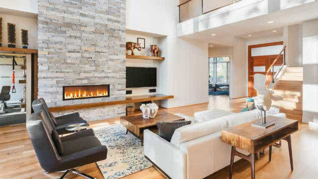 An image of a lit fireplace in a modern living room. Image: Breadmaker, Shutterstock