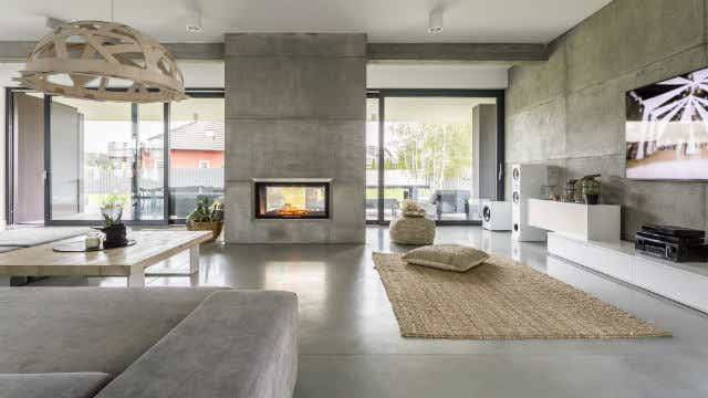 A picture of a modern double-sided fireplace in a modern home with concrete floors. Image: Photographee.eu. (Shutterstock)