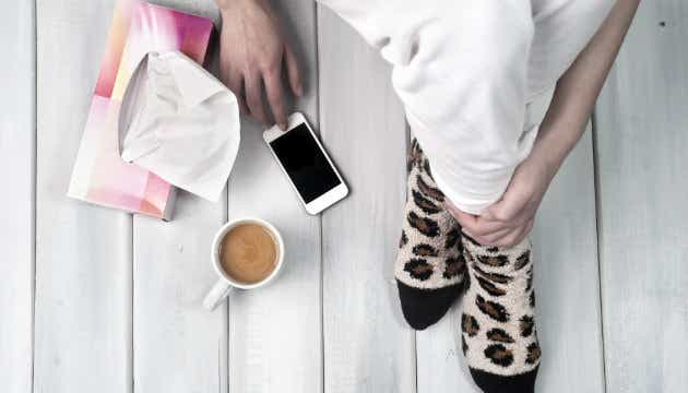 An image of a person with socks on sitting on the ground with a phone, cup of coffee and a box of tissues. | Canstar