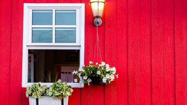 A picture of a red house with an open, double-hung sash window, with a window box of flowers, a lit light and a hanging plant