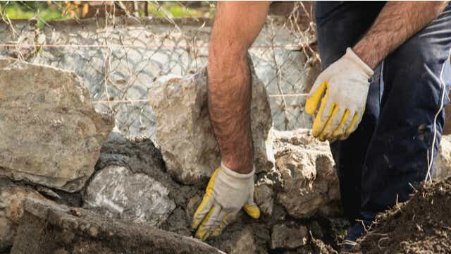 tradie building a stone retaining wall