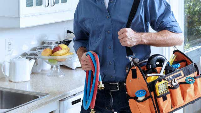 A plumber stands with a took pack next to a kitchen bench featuring a sink