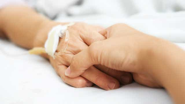 Two people holding hands in a hospital bed