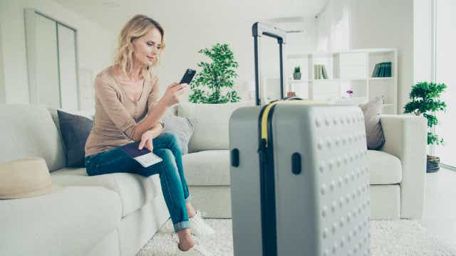 A woman sits on a couch looking at her phone with luggage at the ready.