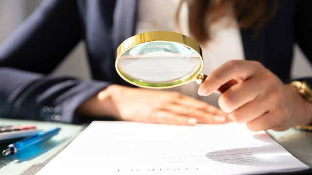 Person looking at paper with magnifying glass