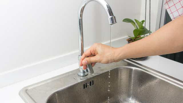 Person turning on tap