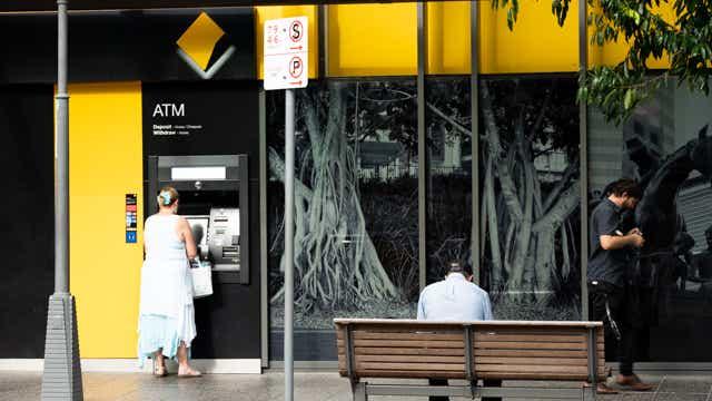 Woman at ATM. CBA has cut savings rates 20 October 2020.