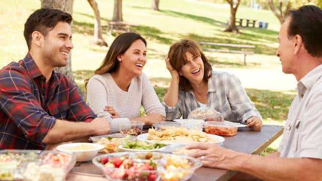 Family enjoys a picnic around a table, news image