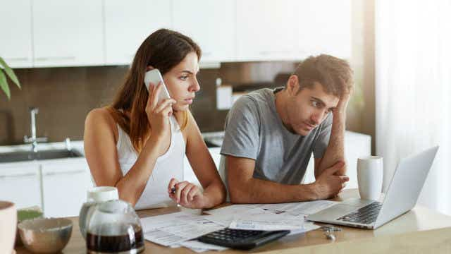 Couple experiencing financial hardship on a phone call.