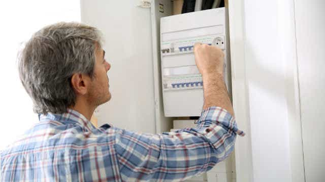Man using electricity box in home