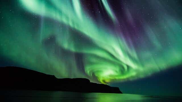 Bright green rays of the Aurora Borealis, twisted into a spiral, shine over Iceland