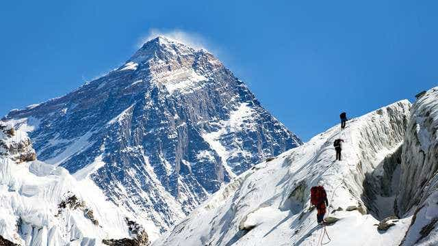 Three mountain climbers make their way up Mt Everest