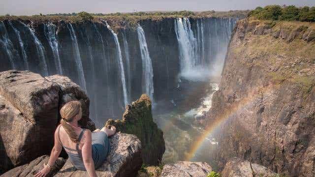 A woman sits atop of Victoria Falls, Mosi-o-tunya Road, Livingstone, Zambia