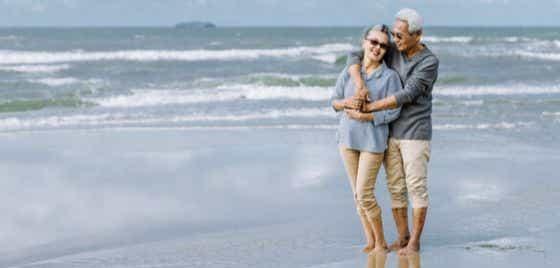 An elderly couple walking on a beach